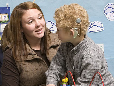 a teacher speaking with a child who has a cochlear implant